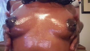 आबनूस लड़की अपने स्तन पर तेल लगाती है